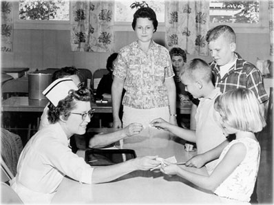 Children being fed sugar cubes with the oral polio vaccine. Circa 1961.